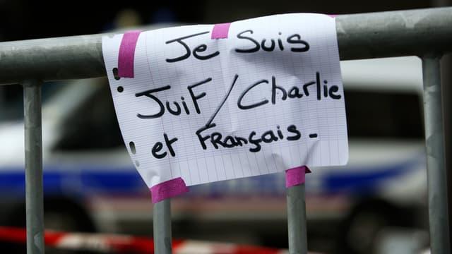 """Une affichette improvisée, marquée d'un """"Je suis juif, Charlie et français"""" et placardée lendemain de la prise d'otages, sur une barrière de sécurité devant l'épicerie casher de la porte de Vincennes, à Paris."""
