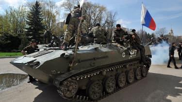 Des hommes armés sur un blindé arborant un drapeau russe à Slavyansk