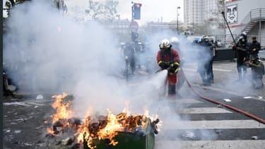 Des pompiers éteignent un feu de poubelle près de la Place d'Italie à Paris, le 16 novembre 2019