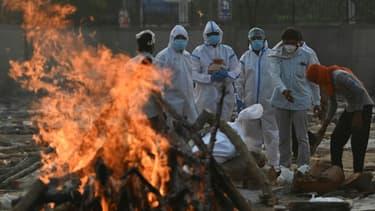 Des proches vêtus d'équipements de protection rendent hommage à une victime du Covid-19 incinérée à New Delhi en Inde le 11 mai 2021