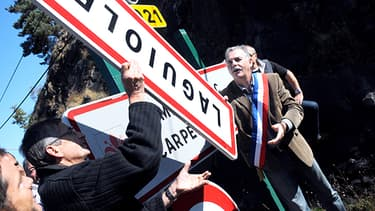 Le maire de Laguiole, Vincent Alazard, retirant le panneau d'entrée de sa commune.