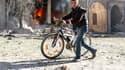 Un jeune homme pousse son vélo près d'une maison en feu, à Alep en Syrie.