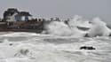 Des passants regardent les vagues s'écraser sur le littoral, le 31 décembre 2017 à Batz-sur-Mer, en Loire-Atlantique.