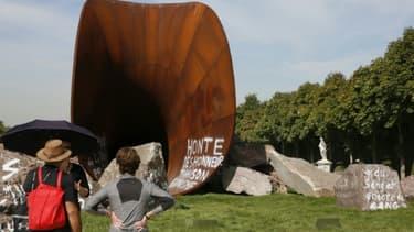 Des visiteurs s'arrêtent devant une des  œuvres de Anish Kapoor vandalisée par des tags antisémites, dans les jardins du Château de Versailles le 11 septembre 2015
