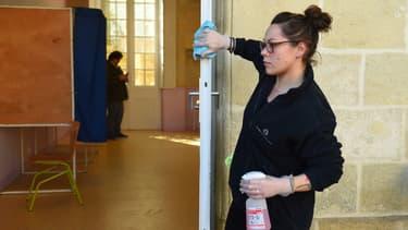 Une femme désinfecte la porte dans un bureau de vote de Bordeaux