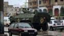 Véhicule militaire dans le faubourg ouvrier d'Ettadamen, près de Tunis. Le président tunisien Zine el Abidine Ben Ali a limogé mercredi son ministre de l'Intérieur au lendemain des premières émeutes à Tunis, où l'armée a fait son apparition. /Photo prise
