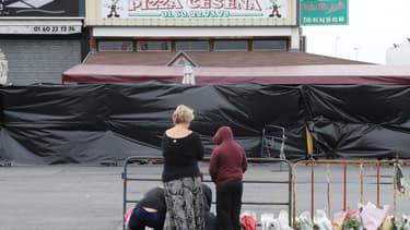 Des passants se recueillent devant la pizzeria où une voiture-bélier a foncé sur la vitrine, tuant une adolescente et blessant grièvement plusieurs personnes.