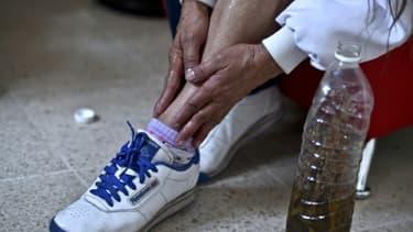 Une femme enduit sa jambe d'alcool dans lequel de la marijuana a macéré pour soulager ses douleurs musculaires à Mexico le 30 novembre 2015