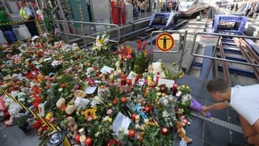 Un homme déposant des fleurs sur le lieu de l'homicide