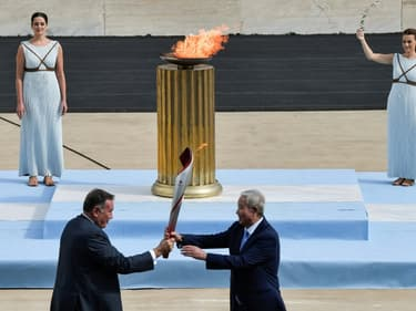 Le vice-président du Comité olympique chinois Yu Zaiqing (à droite) reçoit la torche olympique des mains du patron de l'olympisme grec Spyros Capralos, lors d'une cérémonie à huis clos à Athènes, le 19 octobre 2021