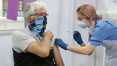 La soignante Nicole Clark administre un vaccin Covid-19 au résident de Glasgow John Loch, au NHS Louisa Jordan Hospital de Glasgow, le 10 février 2021.