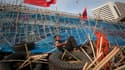 """Une """"chemise rouge"""" sur une barricade de bambous et de pneus érigée dans le quartier de Silom à Bangkok. La crainte d'un violent affrontement devient plus pressante en Thaïlande, où les manifestants anti-gouvernementaux ont bloqué l'entrée de convois de p"""