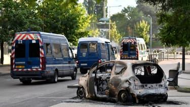 Des véhicules de police passent à proximité d'une voiture incendiée dans le quartier des Grésilles, le 15 juin 2020 à Dijon