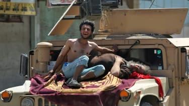 Des civils blessés lorsqu'un kamikaze s'est fait exploser, attendent des secours installés sur le capot d'un véhicule des forces de sécurité irakiennes, le 23 juin 2017 à Mossoul