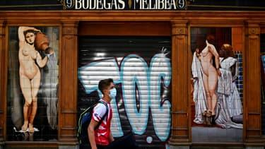 Un jeune homme passe devant un bar fermé à Madrid, en Espagne, le 9 juillet 2020