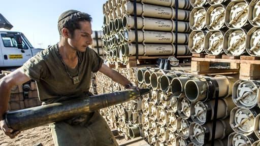 Un soldat israélien transporte des obus pour la préparation d'un tank Merkava à la frontière entre Israël et Gaza, le 31 juillet.