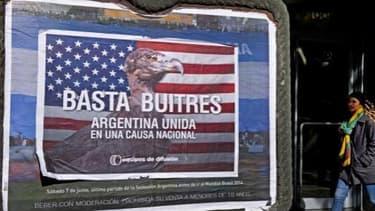 """A Buenos Aires, une passante marche à côté d'un poster qui dénoncer les """"fonds vautours""""."""