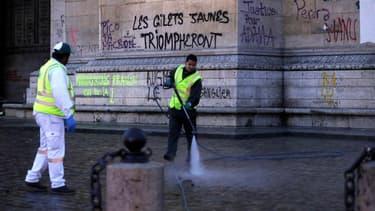 Des agents d'entretien nettoient les graffitis sur l'Arc de Triomphe, le dimanche 2 décembre.