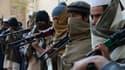 Des anciens soldats talibans posent avec leurs armes.