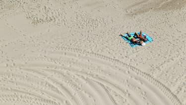 Des touristes prennent le soleil sur la plage d'en Bossa à Ibiza (Espagne) le 30 juillet 2020 (PHOTO D'ILLUSTRATION)