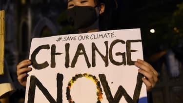 Une manifestante tient une pancarte pendant une manifestation durant la semaine mondiale de grève pour le climat, à Hanoi, le 27 septembre 2019