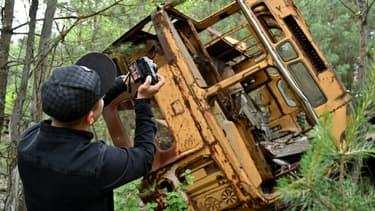 Un touriste prend une photo d'un bus abandonné à Pripyat durant un tour dans la zone d'exclusion de Tchernobyl.