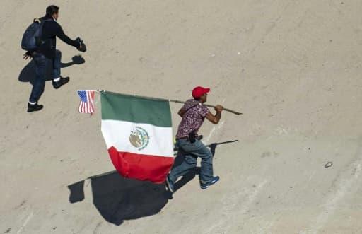 Un migrant portant les drapeaux mexicain et étatsunien tente de passer la frontière entre le Mexique et les Etats-Unis le 25 novembre 2018 à Tijuana