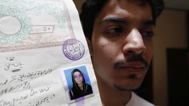 Hassan Khan montre un document avec une photo de sa défunte femme, Zeenat Bibi.