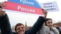 """Deux femmes brandissent des banderoles sur lesquelles est écrit: """"Crimée, Russie"""" (à gauche) et """"Crimée, Russie avec vous"""" (droite) pendant une manifestation à Moscou, le 7 mars 2014."""