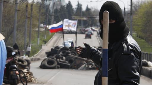Un activiste pro-russe accompli un geste menaçant alors qu'il garde un barricade à Slaviansk dans l'est de l'Ukraine, le 14 avril 2014.