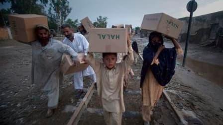 A Nowshera, dans le nord-ouest du Pakistan, des habitants regagnent leur domicile avec des vivres distribués par l'armée. Selon l'Unicef, plus de trois millions de personnes ont été touchées par les importantes inondations survenues dans le nord-ouest du
