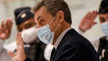 L'ancien président Nicolas Sarkozy salue d'un geste les policiers au dernier jour de son procès pour corruption le 10 décembre 2020 au Palais de justice de Paris