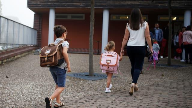 Une mère de famille accompagne ses enfants à l'école. (PHOTO D'ILLUSTRATION)