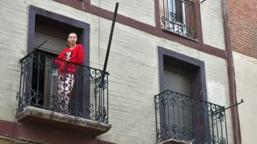 Une personne atteinte du coronavirus et placée en confinement prend l'air sur son balcon.