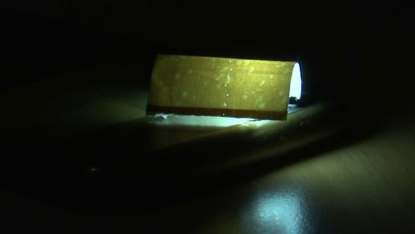 En plaçant une lumière à l'intérieur du papier du filtre, on peut distinguer les minuscules trous d'aération litigieux.