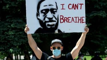"""Un manifestant porte une pancarte à l'effigie de George Floyd, le 30 mai 2020 à Denver, dans le Colorado, avec ses derniers mots: """"Je ne peux pas respirer"""""""