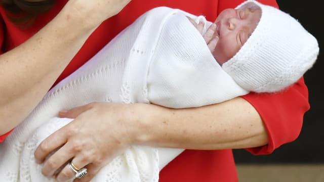 Le prince Louis de Cambridge dans les bras de sa mère Kate Middleton, le 23 avril 2018