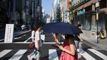 Une femme en train de traverser la rue près de Tokyo, les yeux rivés sur son smartphone.