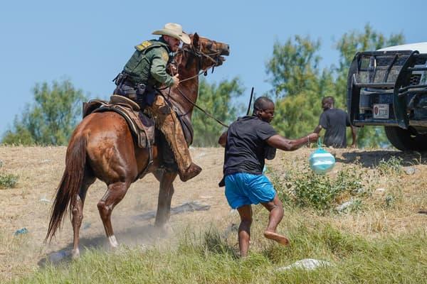 Un agent de la police des frontières américain à cheval essayant d'empêcher un homme de rejoindre le camp actuel près du fleuve Rio Grande, le 19 septembre 2021
