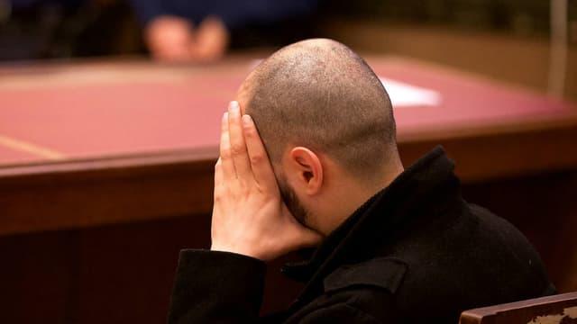 Un des accusés se tient le visage lors de l'introduction du procès de la cellule de Verviers, le 15 avril 2016, au tribunal correctionnel de Bruxelles.