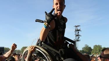Les festivaliers hissent une spectatrice en fauteuil, pendant le Hellfest 2017 à Clisson, le 17 juin.