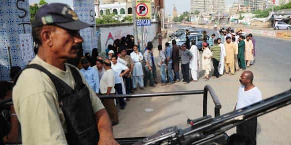 Des habitants de Karachi font la queue devant un bureau de vote, samedi, sous la protection d'un membre des forces de l'ordre.
