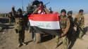 Des membres des forces irakiennes posent avec le drapeau national à Ramadi, après leur victoire sur Daesh, le 29 décembre.