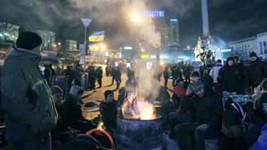 Les manifestants ukrainiens se réchauffent à côté d'un feu sur la place de l'Indépendance à Kiev, le 14 décembre.