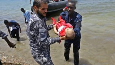 Le corps d'un des trois bénés repêchés vendredi après le naufrage d'une embarcation est porté par des membres des forces de sécurité libyennes, le 29 juin 2018 à al-Hmidiya