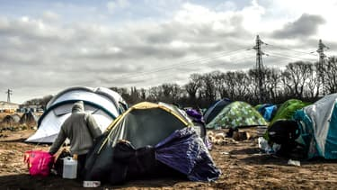 Un migrant devant une tente dans un campement informel, près du port de Calais, le 18 février 2019