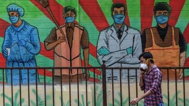 Un piéton portant un masque de protection passe devant une fresque murale représentant diverses professions mobilisées contre la pandémie de Covid-19, à Bombay (Inde) le 21 mars 2021