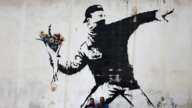 """""""Le lanceur de fleurs"""", le célèbre graffiti de Banksy, peint sur un mur à Bethléem, en 2015."""