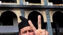 Manifestant devant le siège incendié du gourvernorat Zaouiyah, à une cinquantaine de km à l'ouest de Tripoli. Les forces de Mouammar Kadhafi semblaient avoir encore perdu du terrain dimanche en Libye mais le dirigeant libyen, au pouvoir depuis 1969, a une