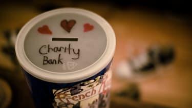 """Une photographie de boite à sous avec une inscription """"banque de la charité"""" sur le couvercle"""